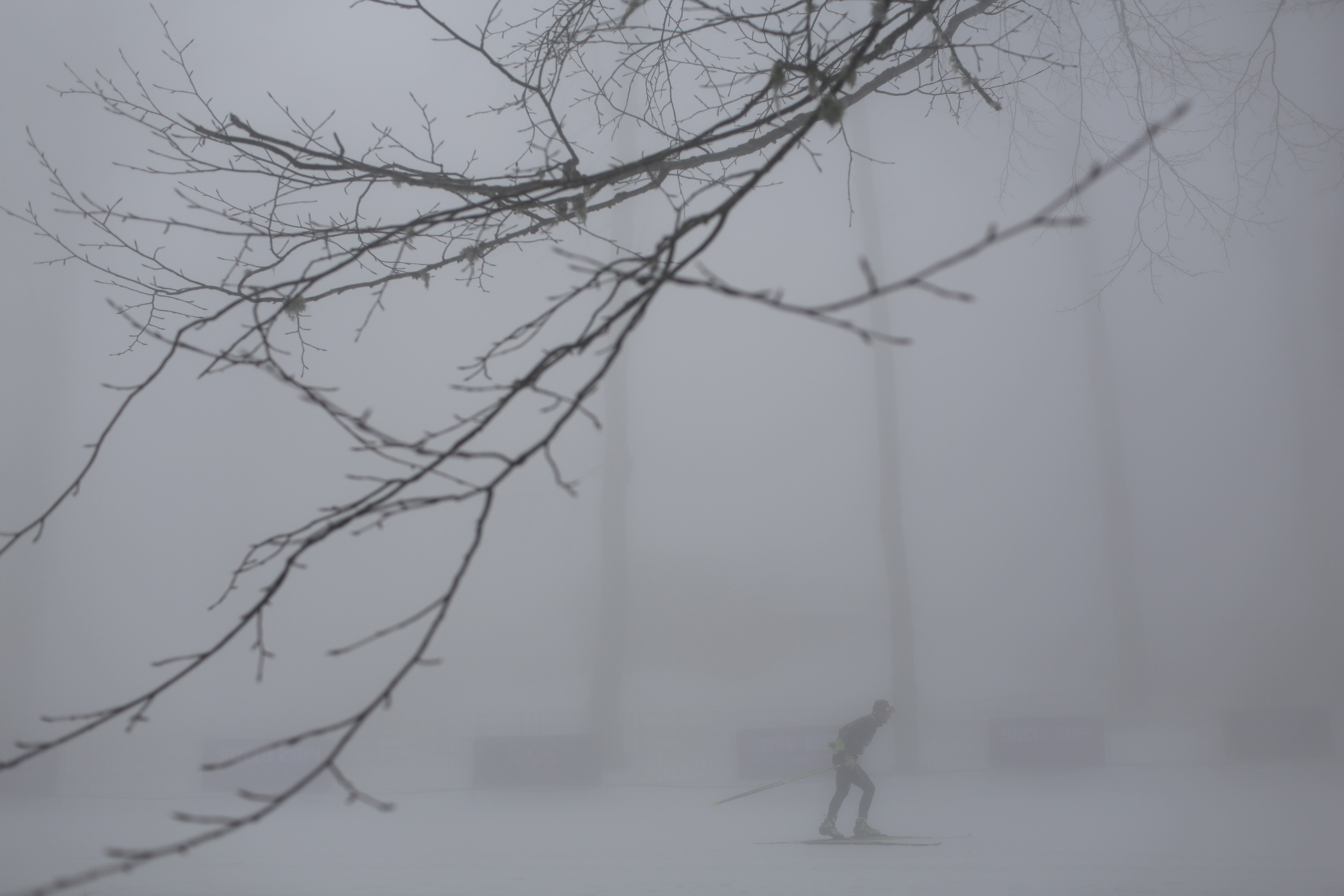 An athlete skis in thick fog at the Laura biathlon center, at the 2014 Winter Olympics, Monday, Feb. 17, 2014, in Krasnaya Polyana, Russia. The men's 15-kilometer mass-start biathlon race at the Sochi Olympics has been delayed due to fog, one day after the event had been called off for the same reason. (AP Photo/Felipe Dana)