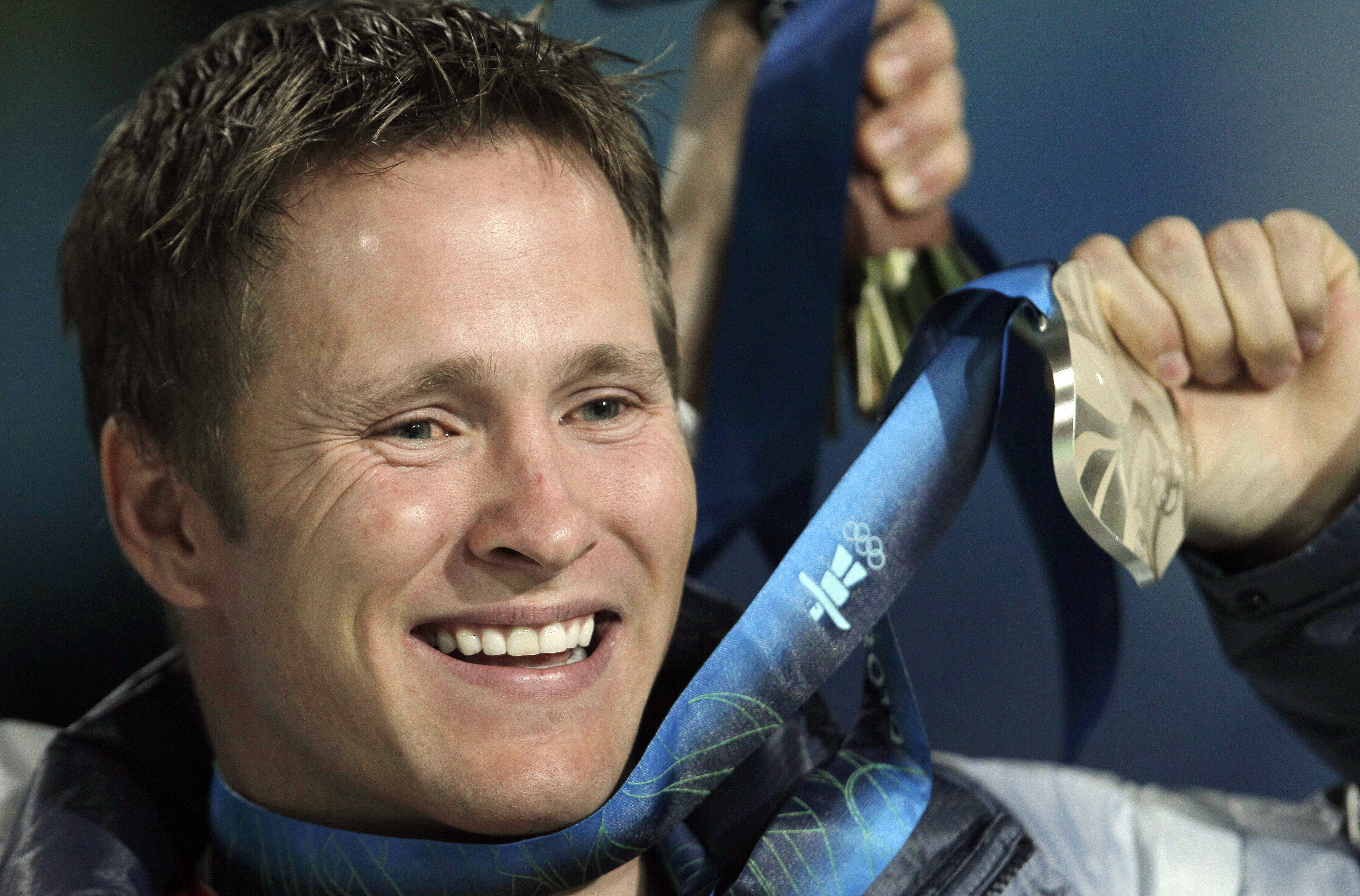 """FILE - In this Feb. 26, 2010, file photo, Jeret Peterson of the Boise, Idaho, holds his silver medal during the medals ceremony for the men's freestyle skiing aerials at the 2010 Winter Olympics in Vancouver, British Columbia. As aerialists get ready to compete at the Sochi Olympics on Monday, Feb. 17, 2014, Peterson will surely be missed. The sport's foremost boundary pusher, and the inventor of the three-flip, five-twisting """"Hurricane"""" jump, took his life in 2011. (AP Photo/Gerry Broome, File)"""
