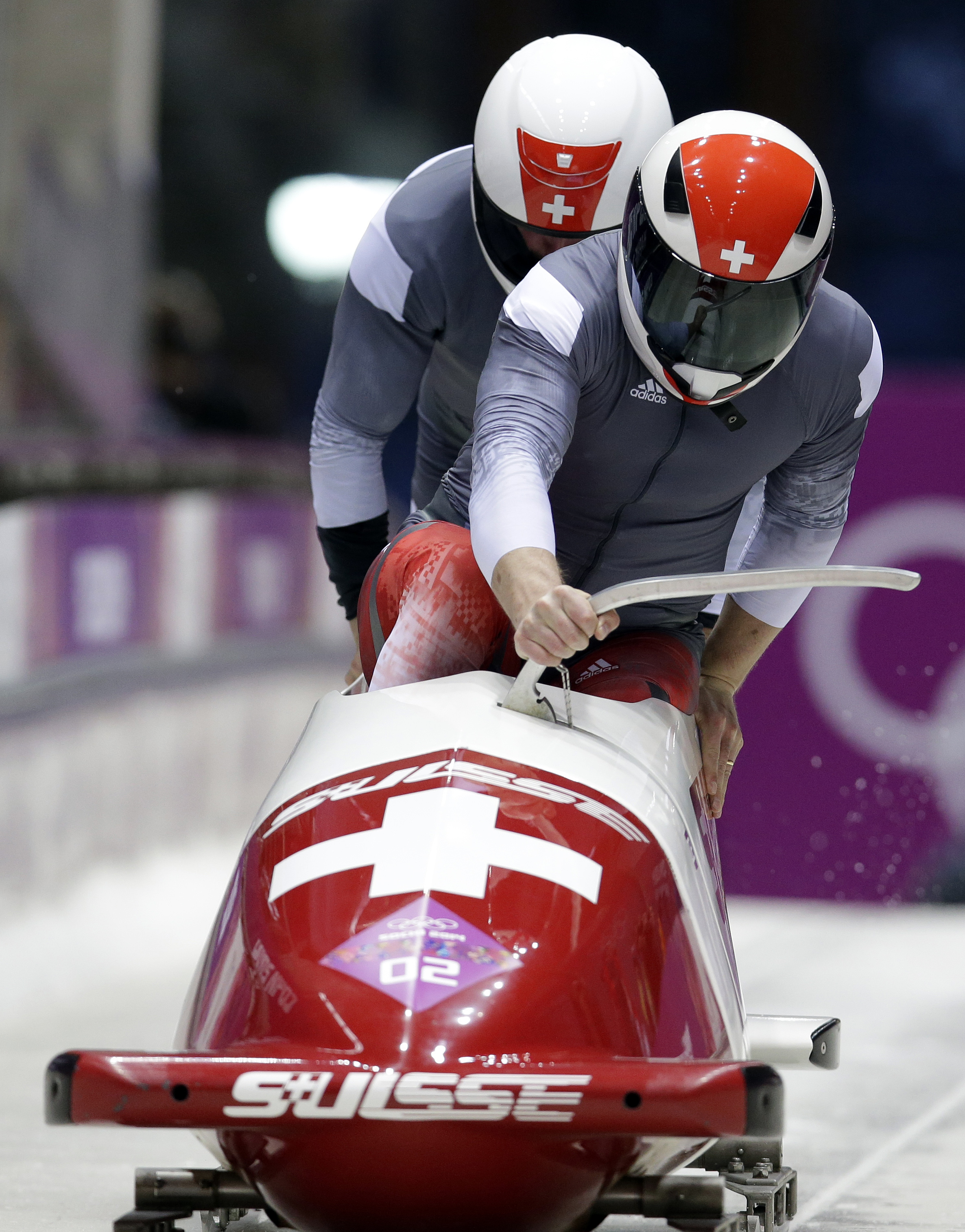 The team from Switzerland SUI-1, piloted by Beat Hefti and brakeman Alex Baumann, start their third run during the men's two-man bobsled competition at the 2014 Winter Olympics, Monday, Feb. 17, 2014, in Krasnaya Polyana, Russia. (AP Photo/Michael Sohn)