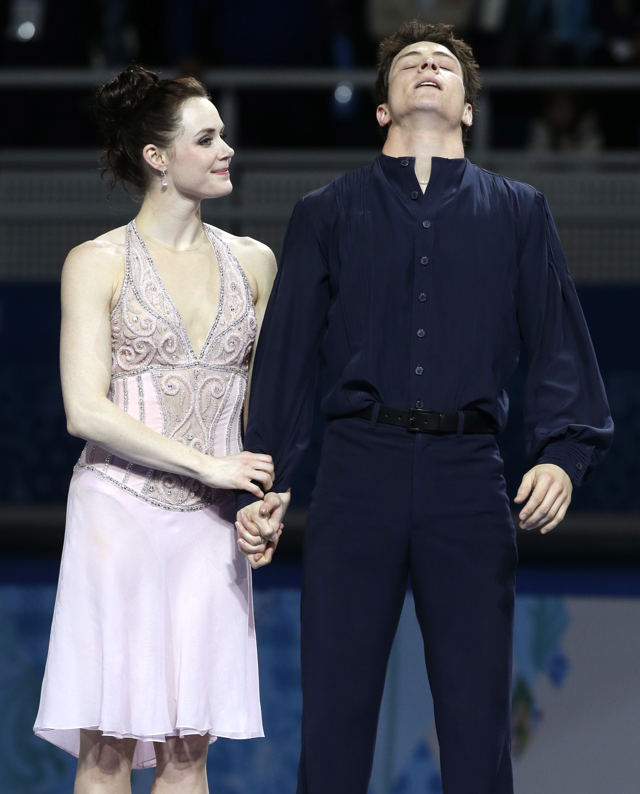 Tessa Virtue and Scott Moir of Canada react after placing second during the flower ceremony ice dance free dance figure skating finals at the Iceberg Skating Palace during the 2014 Winter Olympics, Monday, Feb. 17, 2014, in Sochi, Russia. (AP Photo/Darron Cummings)