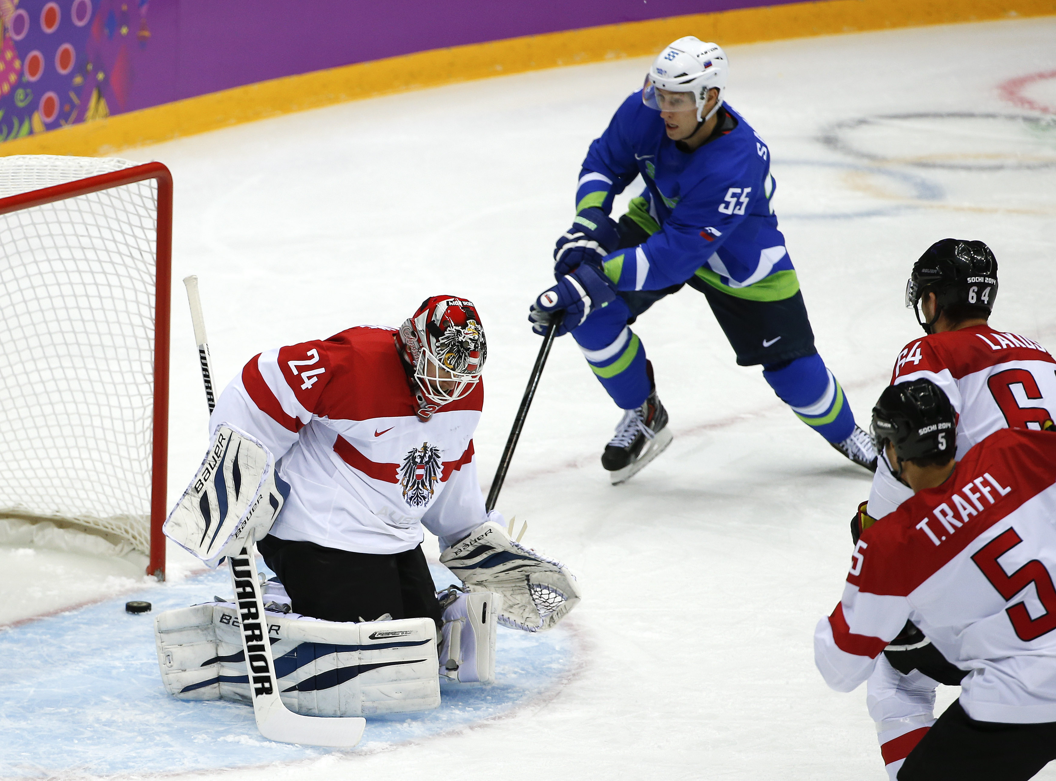 The puck, shot by Slovenia forward Anze Kopitar, slips past Austria goaltender Mathias Lange for a goal in the first period period of a men's ice hockey game at the 2014 Winter Olympics, Tuesday, Feb. 18, 2014, in Sochi, Russia. (AP Photo/Julio Cortez)