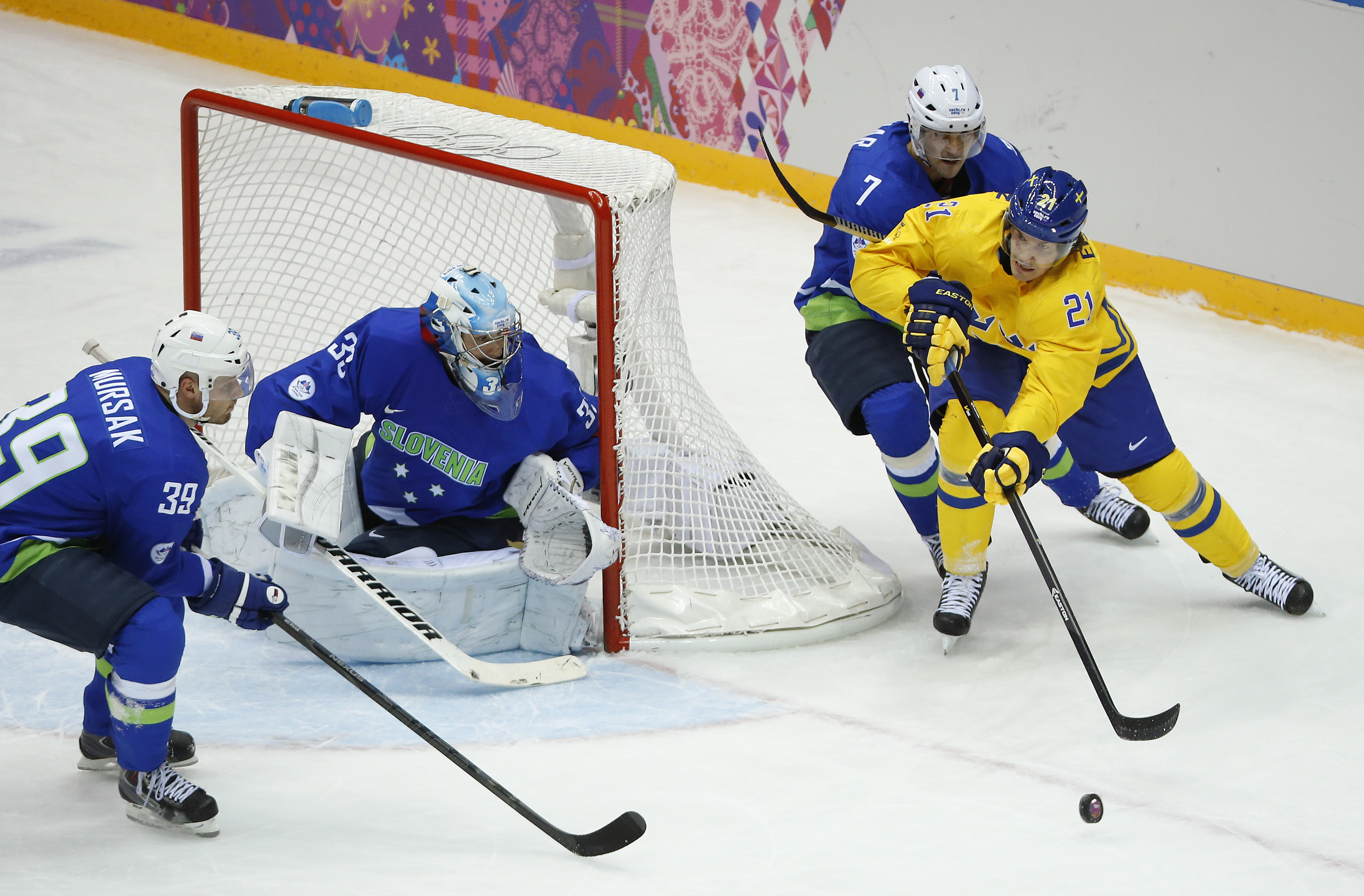 Sweden forward Loui Eriksson (21) looks to pass against Slovenia defenseman Klemen Pretnar (7) in the first period of a men's quarterfinal ice hockey game at the 2014 Winter Olympics, Wednesday, Feb. 19, 2014, in Sochi, Russia. (AP Photo/Mark Humphrey)