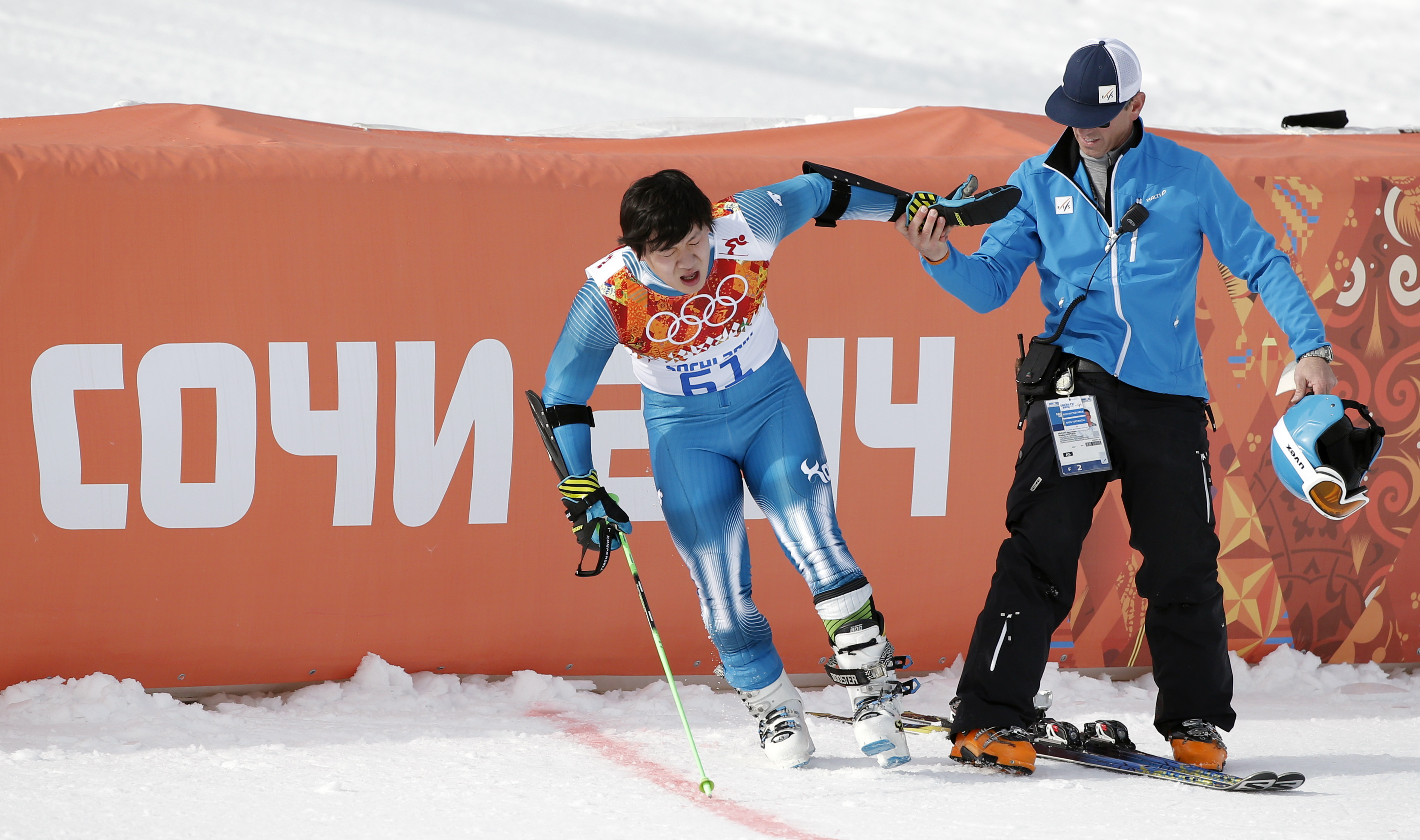 An official assists South Korea's Kyung Sung-yun after he crashed  in the first run of the men's giant slalom at the Sochi 2014 Winter Olympics, Wednesday, Feb. 19, 2014, in Krasnaya Polyana, Russia. (AP Photo/Christophe Ena)