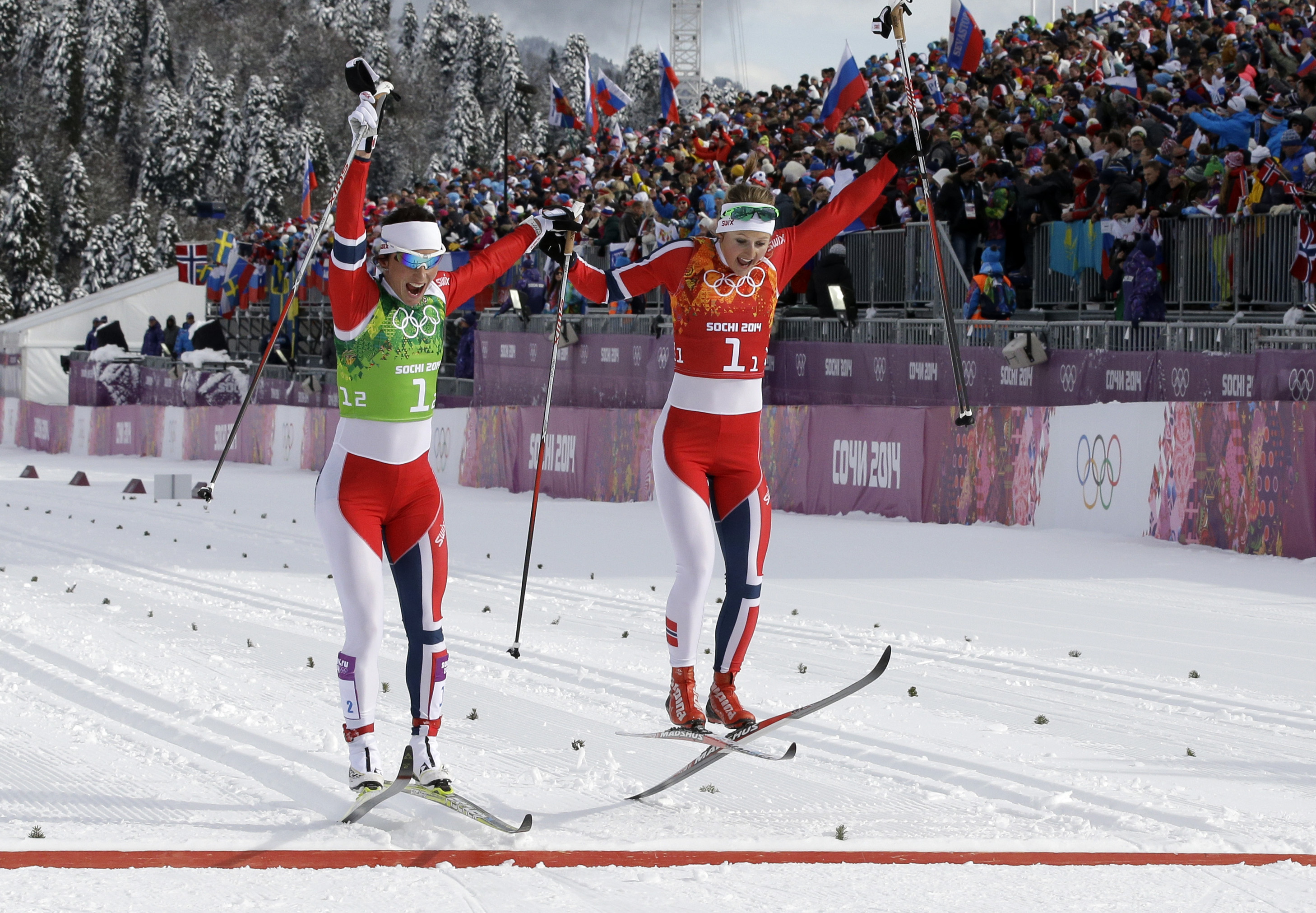Norway's Marit Bjoergen, left, and Ingvild Flugstad Oestberg celebrate winning the gold medal in the cross-country team sprint competitions at the 2014 Winter Olympics, Wednesday, Feb. 19, 2014, in Krasnaya Polyana, Russia. (AP Photo/Lee Jin-man)