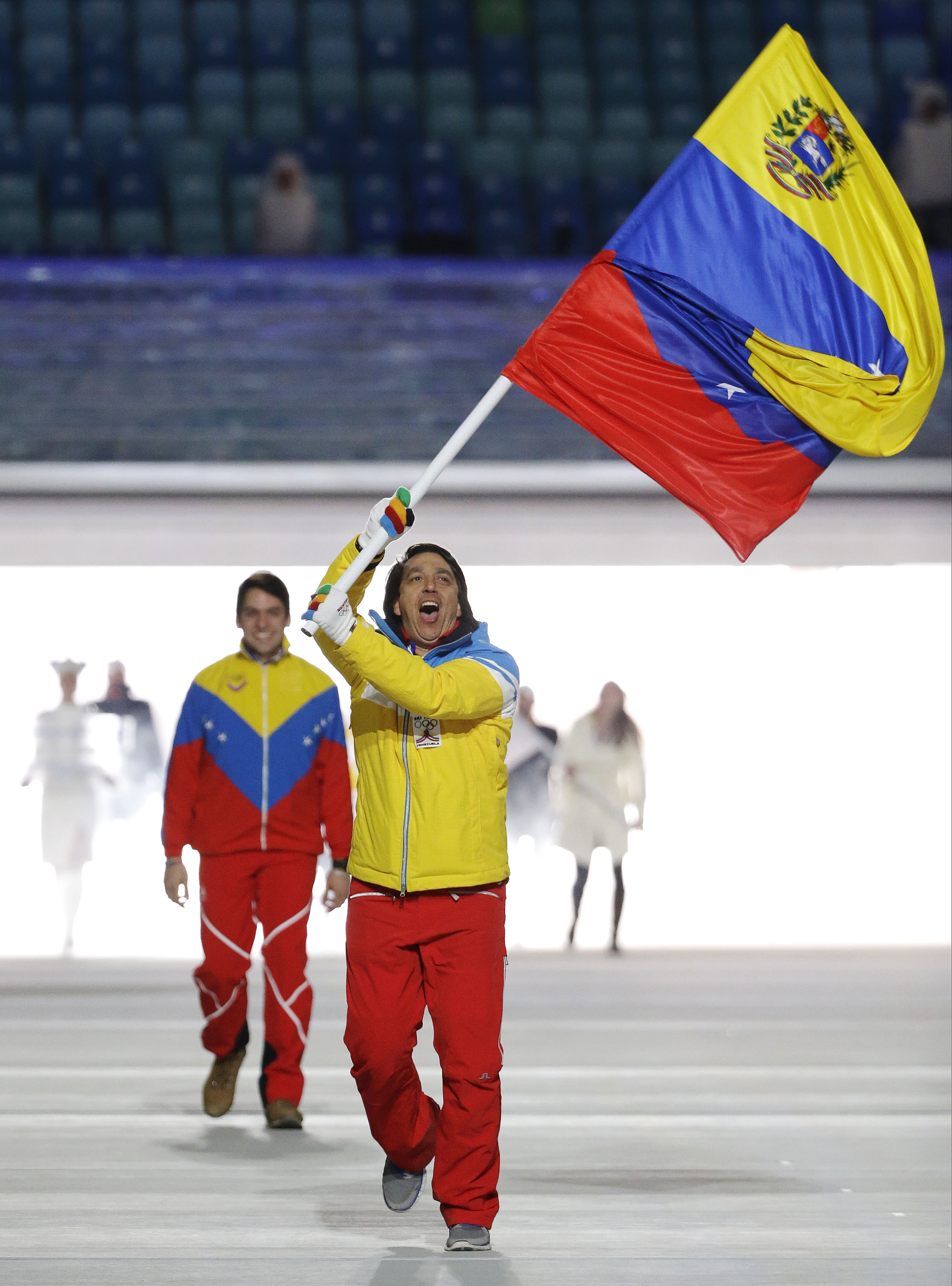 FILE - In this Feb. 7, 2014 file photo, Antonio Pardo of Venezuela carries a representation of his country's national flag as he leads the team during the opening ceremony of the 2014 Winter Olympics in Sochi, Russia. There have been Venezuelan athletes at past Winter Olympics, but Pardo is the first to enter an Alpine skiing event. (AP Photo/Mark Humphrey, File)