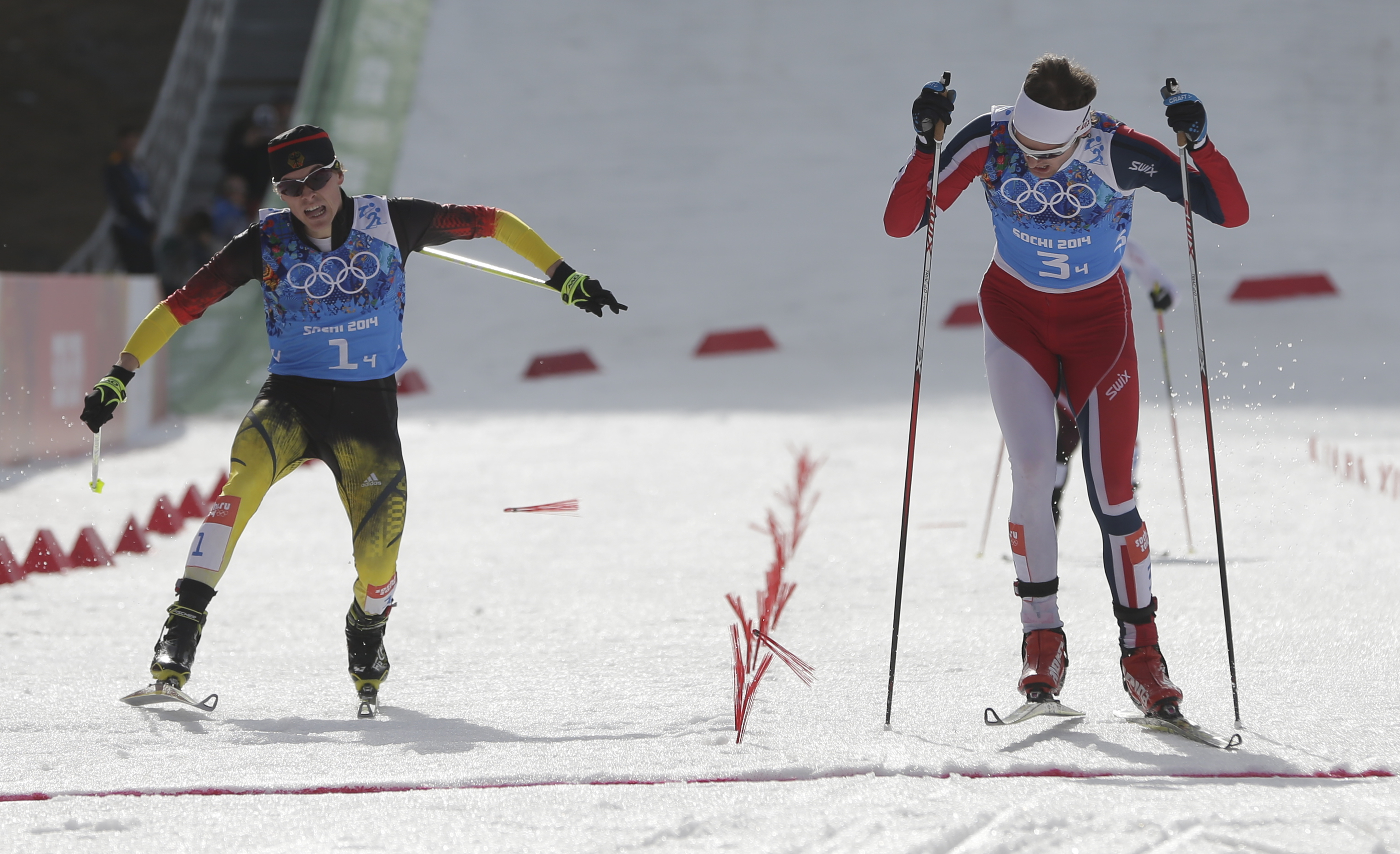 Norway's Joergen Graabak, right, crosses the finish line to win gold ahead of silver medal winner Germany's Fabian Riessle, left, during the cross-country portion of the Nordic combined Gundersen large hill team competition at the 2014 Winter Olympics, Thursday, Feb. 20, 2014, in Krasnaya Polyana, Russia. (AP Photo/Matthias Schrader)