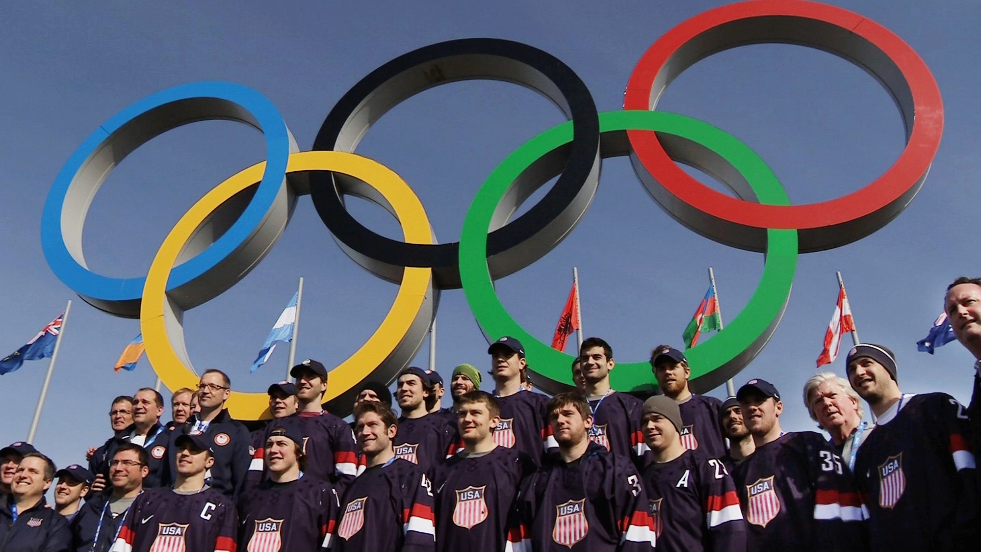 In this still image taken from video, members of the men's ice hockey team from the United States post in front of the Olympic rings in Olympic Park during the 2014 Winter Olympics in Sochi, Russia, on Thursday, Feb. 20, 2014. The U.S. and Canada will play each other in the semifinal round on Friday, Feb. 21. (AP Photo/Ben Jary)