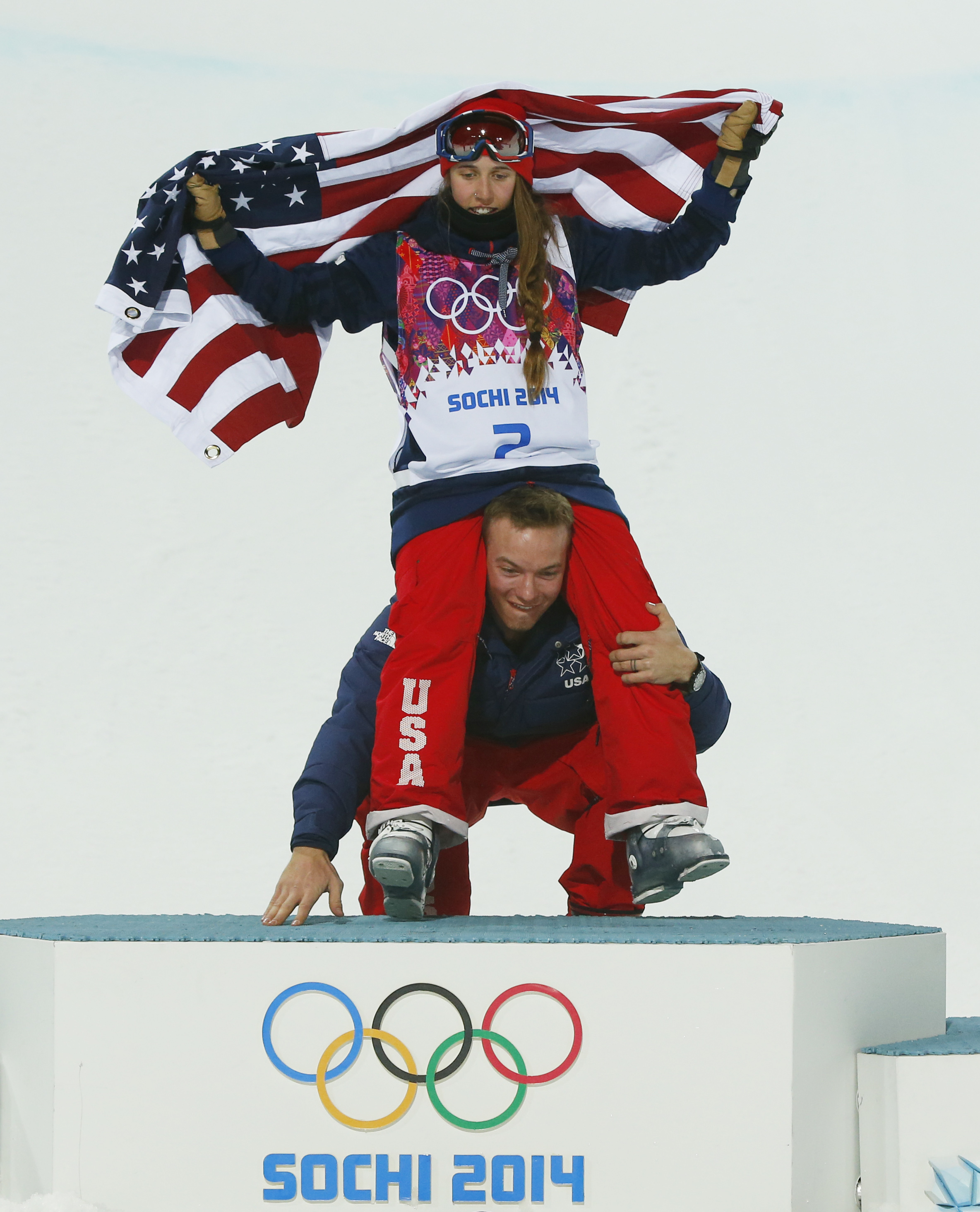 David Wise of the United States, the men's halfpipe gold medal winner, picks up Maddie Bowman of the United States after she won the gold medal in the women's ski halfpipe final, at the Rosa Khutor Extreme Park, at the 2014 Winter Olympics, Thursday, Feb. 20, 2014, in Krasnaya Polyana, Russia.(AP Photo/Sergei Grits)