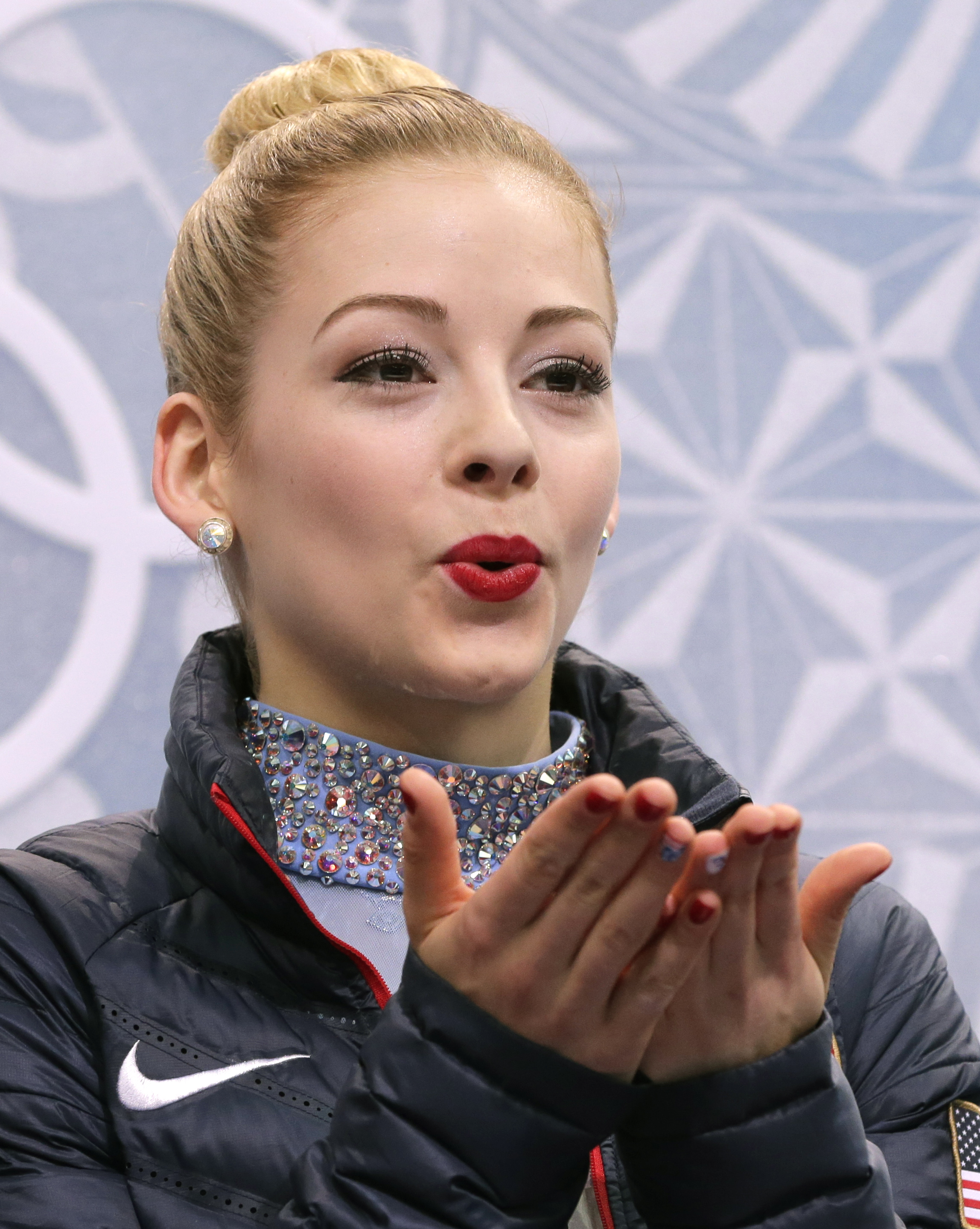 Gracie Gold of the United States blows a kiss to spectators as she waits in the results area after completing her routine in the women's free skate figure skating finals at the Iceberg Skating Palace during the 2014 Winter Olympics, Thursday, Feb. 20, 2014, in Sochi, Russia. (AP Photo/Bernat Armangue)