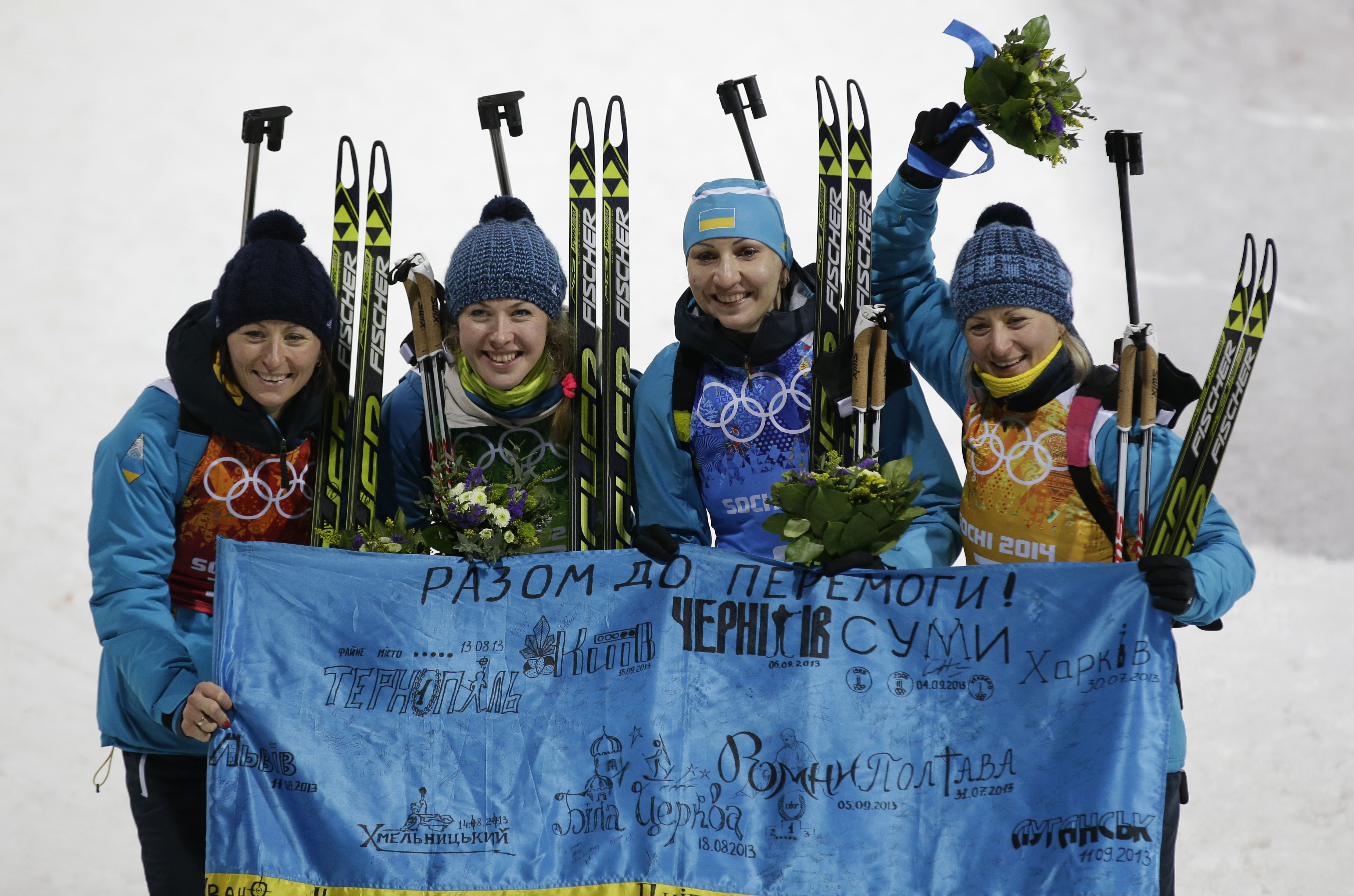 From left, Ukraine's relay team Vita Semerenko, Juliya Dzhyma, Olena Pidhrushna and Valj Semerenko pose with an Ukraine's flag, after winning the gold medal in the women's biathlon 4x6k relay at the 2014 Winter Olympics, Friday, Feb. 21, 2014, in Krasnaya Polyana, Russia. (AP Photo/Lee Jin-man)