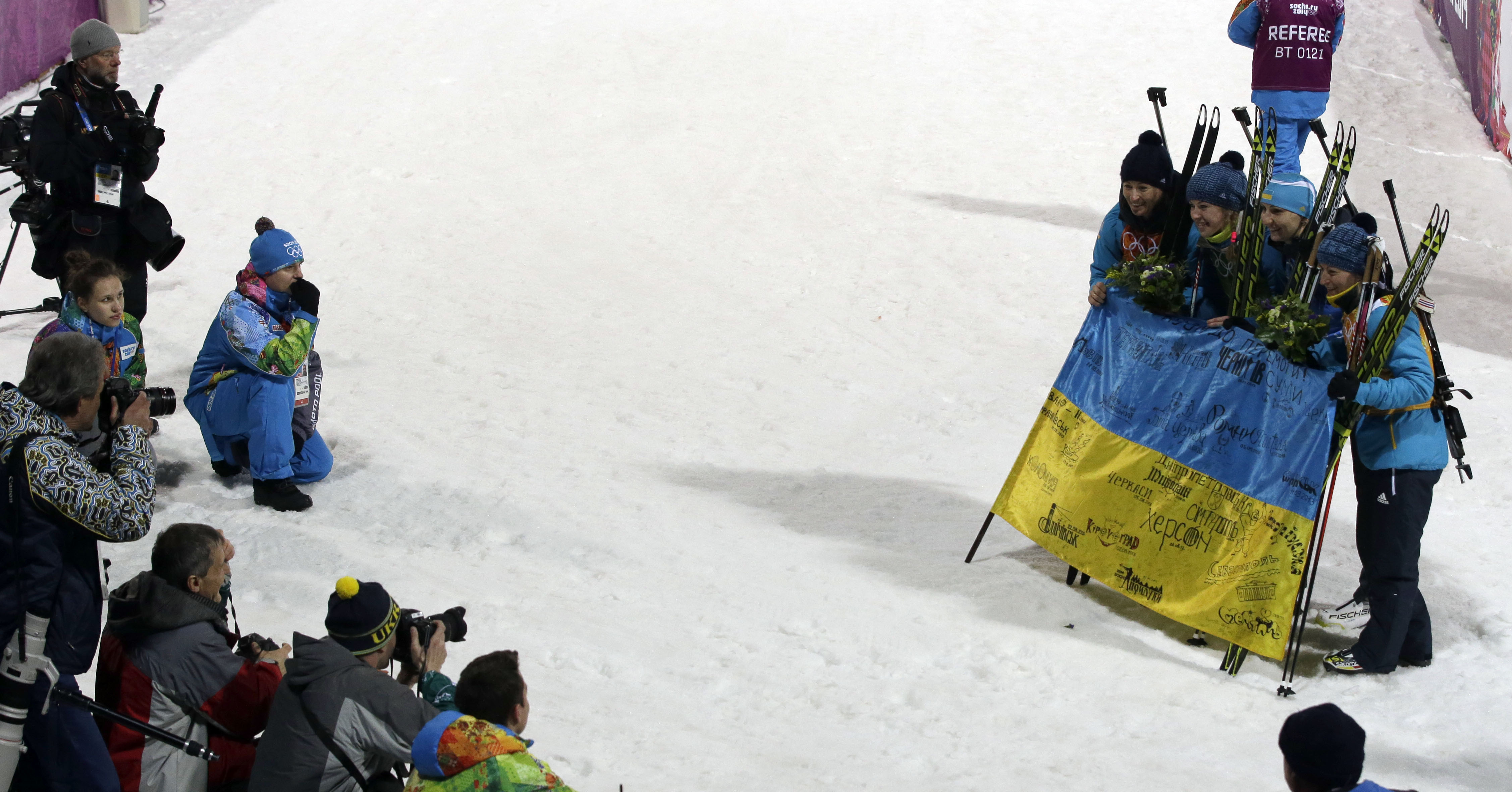 Ukraine's relay team members, from left,  Vita Semerenko, Juliya Dzhyma, Olena Pidhrushna and Valj Semerenko, pose with a Ukraine's flag, after winning the gold medal in the women's biathlon 4x6k relay at the 2014 Winter Olympics, Friday, Feb. 21, 2014, in Krasnaya Polyana, Russia.  (AP Photo/Lee Jin-man)