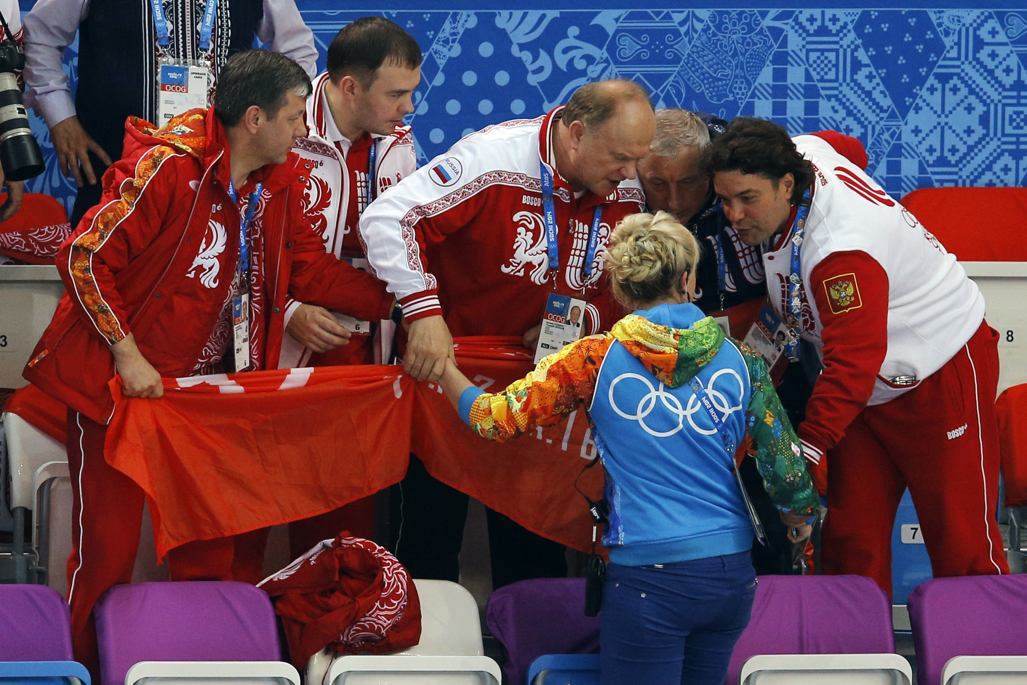 Russian Communist Party leader Gennady Zyuganov, center, and party spokesman Alexander Yushchenko, right, clutch the arms of the protocol manager at the Iceberg Skating Palace in Sochi, Russia, as she tries to stop them from displaying the Soviet Banner of Victory during a flower ceremony for the short track speedskating competition at the 2014 Winter Olympics on Friday, Feb. 21, 2014. The banner is a replica of the flag raised by Soviet soldiers in Berlin in 1945, in victory over Nazi Germany. Communist lawmakers and members of parliament Yuri Afonin, second left, and Nikolai Kharitonov, second right, join the argument. The International Olympic Committee forbids the display of political banners at Olympic venues. (AP Photo/Vadim Ghirda)