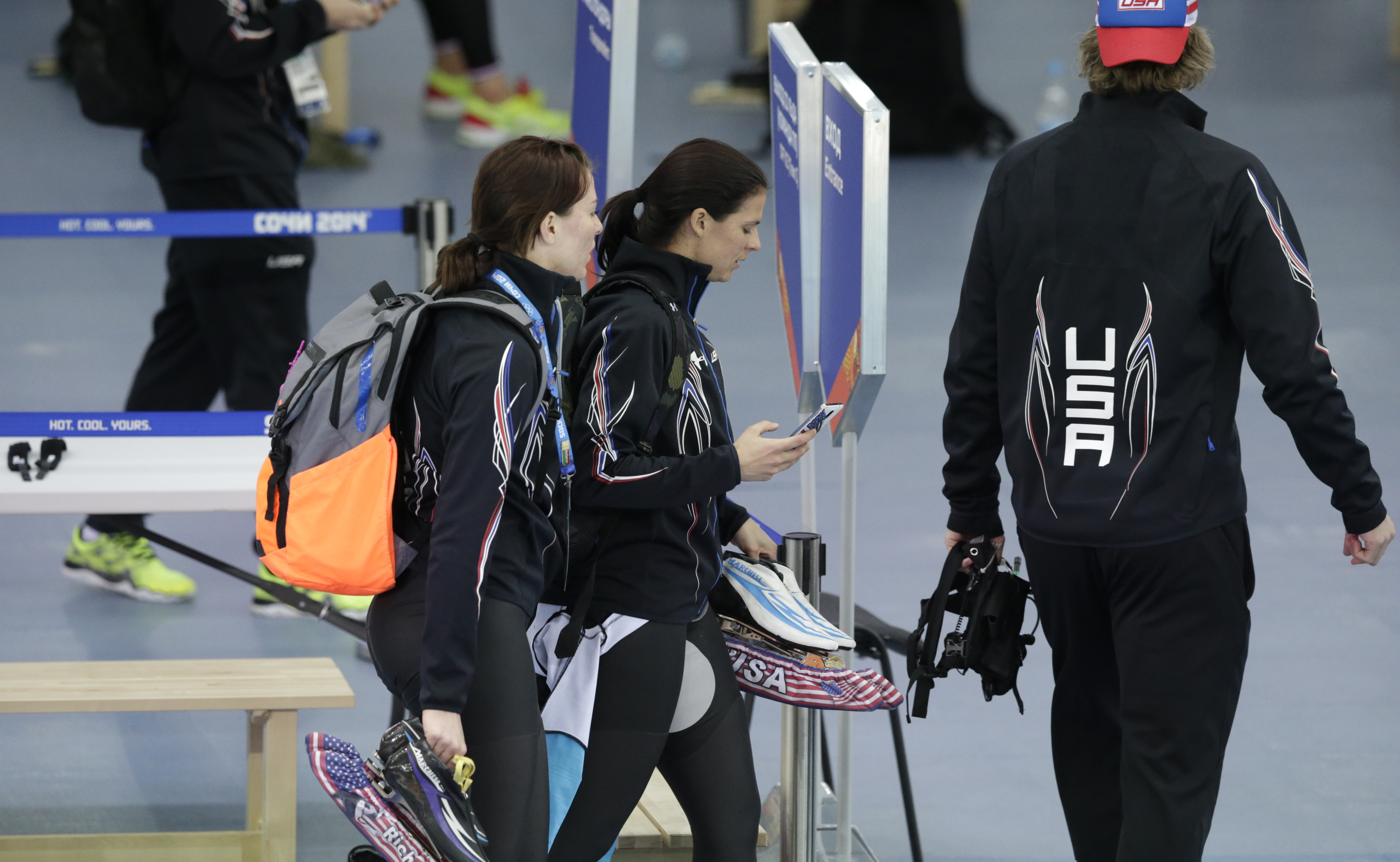 U.S. speedskaters Heather richardson, left, and Brittany Bowe hold their skates and walk out of the arena after competing in the women's team pursuit race to take sixth place against Canada at the Adler Arena Skating Center at the 2014 Winter Olympics, Saturday, Feb. 22, 2014, in Sochi, Russia. (AP Photo/Matt Dunham)