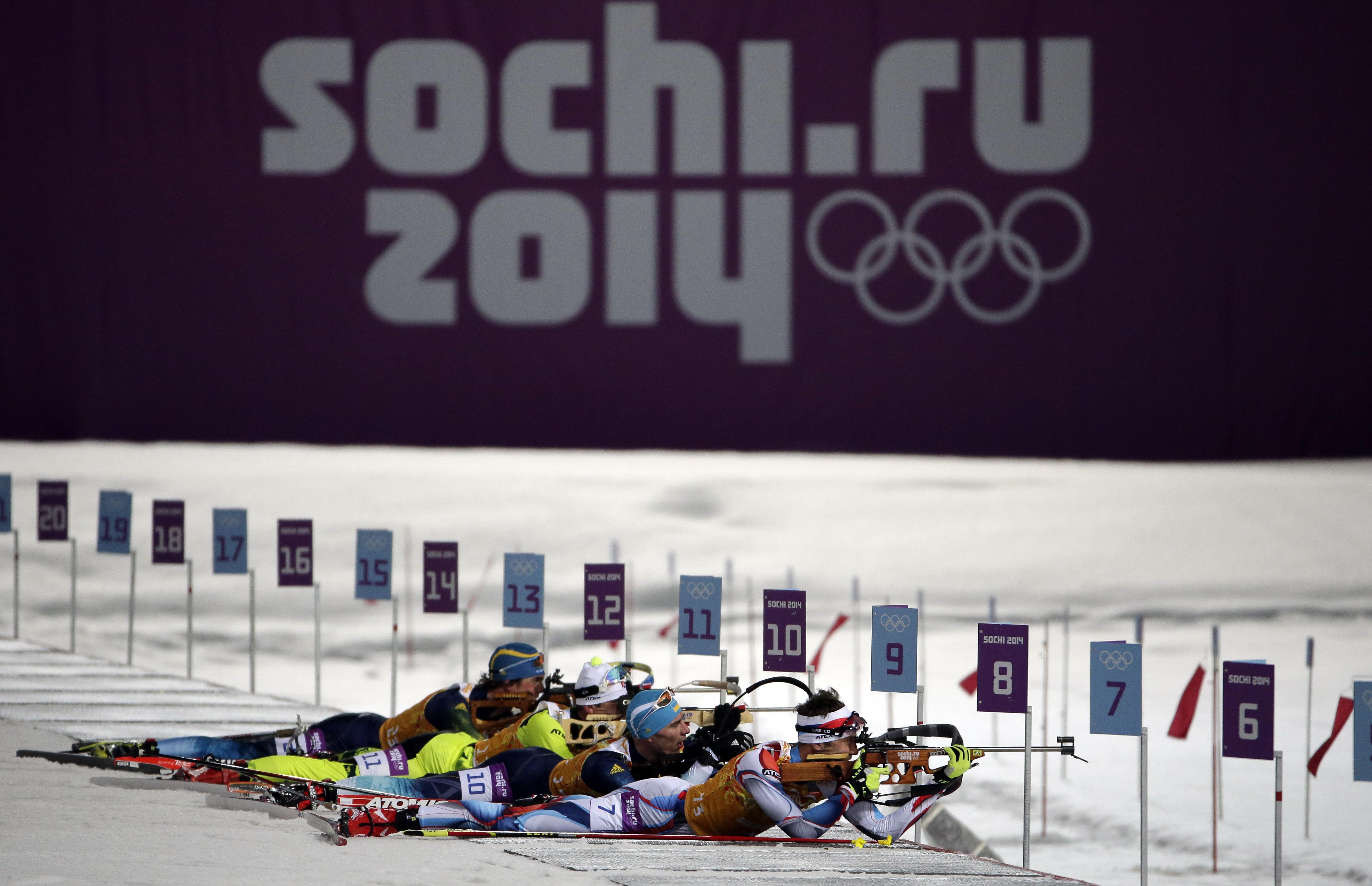 Competitors line up in the shooting range during the men's biathlon 4x7.5K relay at the 2014 Winter Olympics, Saturday, Feb. 22, 2014, in Krasnaya Polyana, Russia. (AP Photo/Felipe Dana)