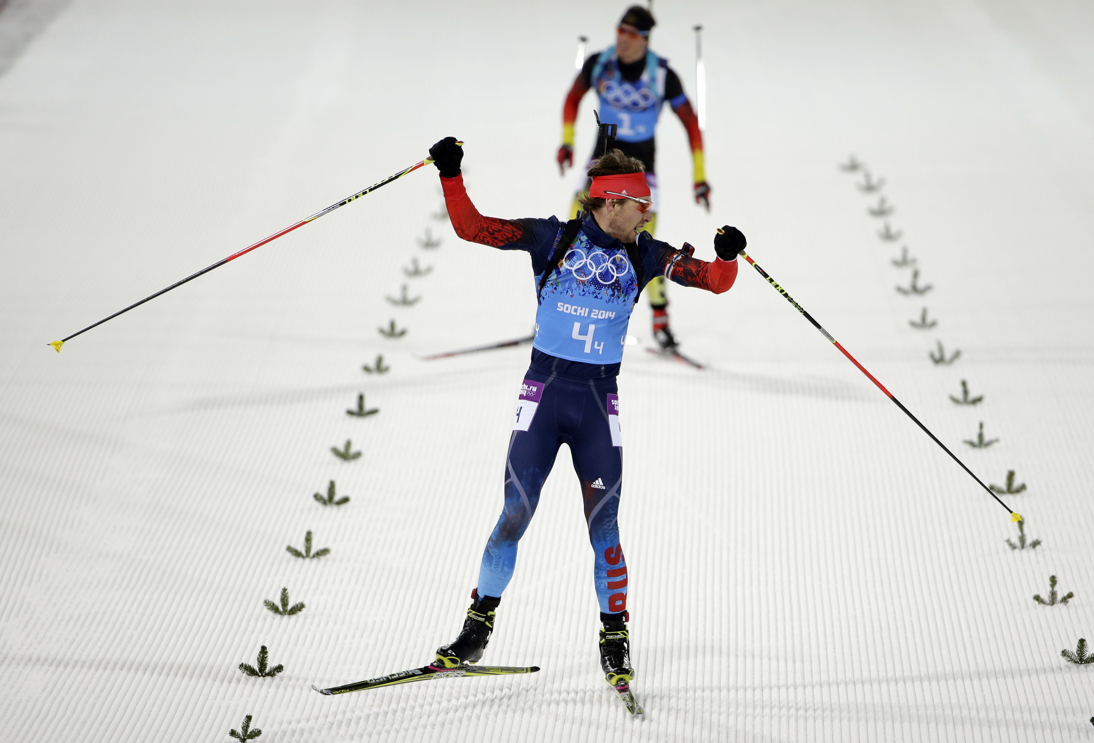 Russia's Anton Shipulin celebrates as he looks back at silver medalist Germany's Simon Schempp, on his way to win the gold in the men's biathlon 4x7.5K relay at the 2014 Winter Olympics, Saturday, Feb. 22, 2014, in Krasnaya Polyana, Russia. (AP Photo/Felipe Dana)