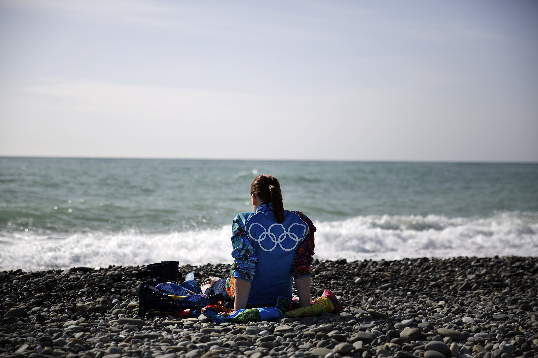 An Olympic volunteer sits on the beach along the Black Sea ahead of tonight's 2014 Winter Olympics closing ceremony, Sunday, Feb. 23, 2014, in Sochi, Russia. (AP Photo/David Goldman)