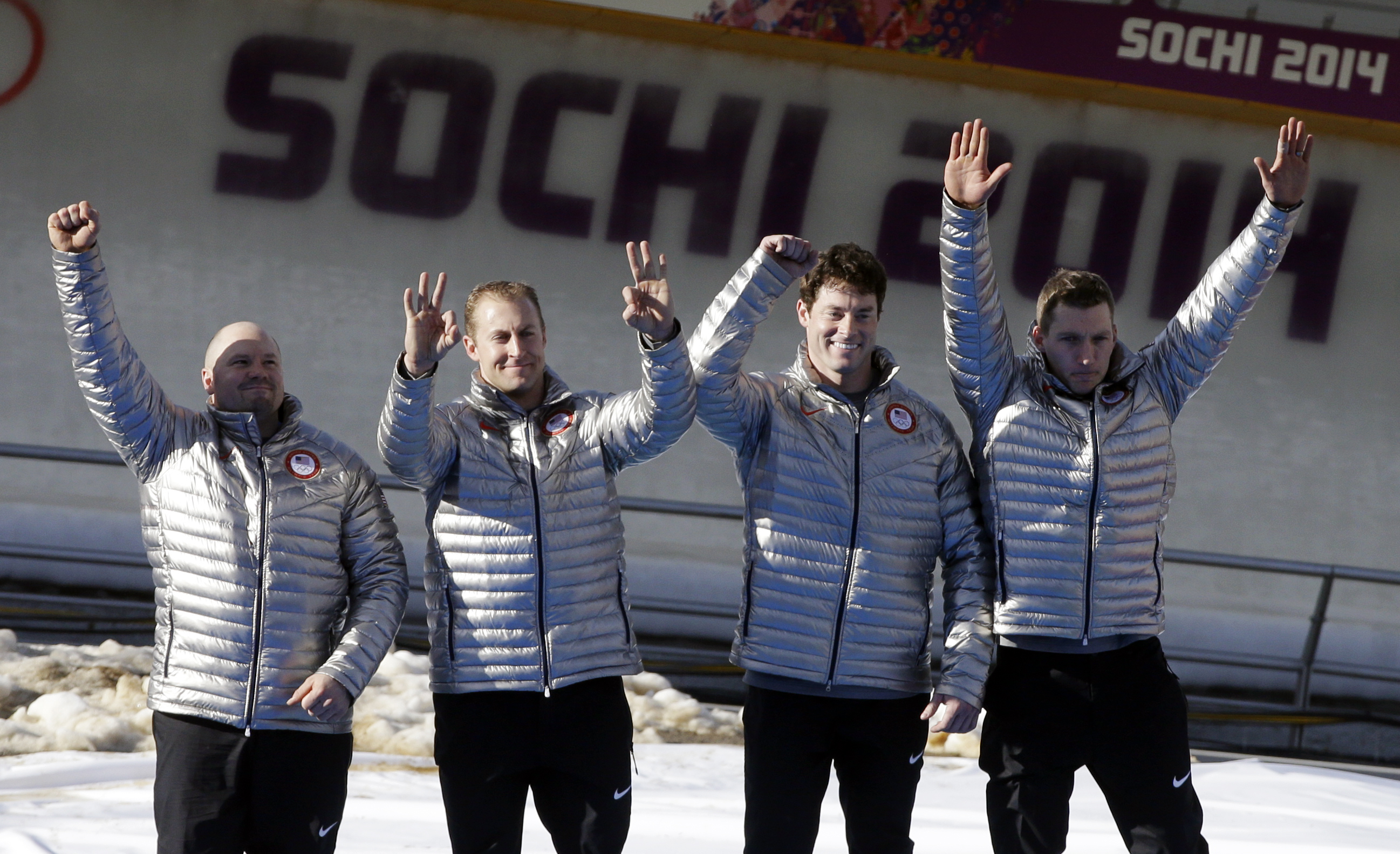 The team from the United States USA-1, with Steven Holcomb, Curtis Tomasevicz, Steven Langton and Christopher Fogt, celebrate after they won the bronze medals in the men's four-man bobsled competition final at the 2014 Winter Olympics, Sunday, Feb. 23, 2014, in Krasnaya Polyana, Russia.(AP Photo/Dita Alangkara)