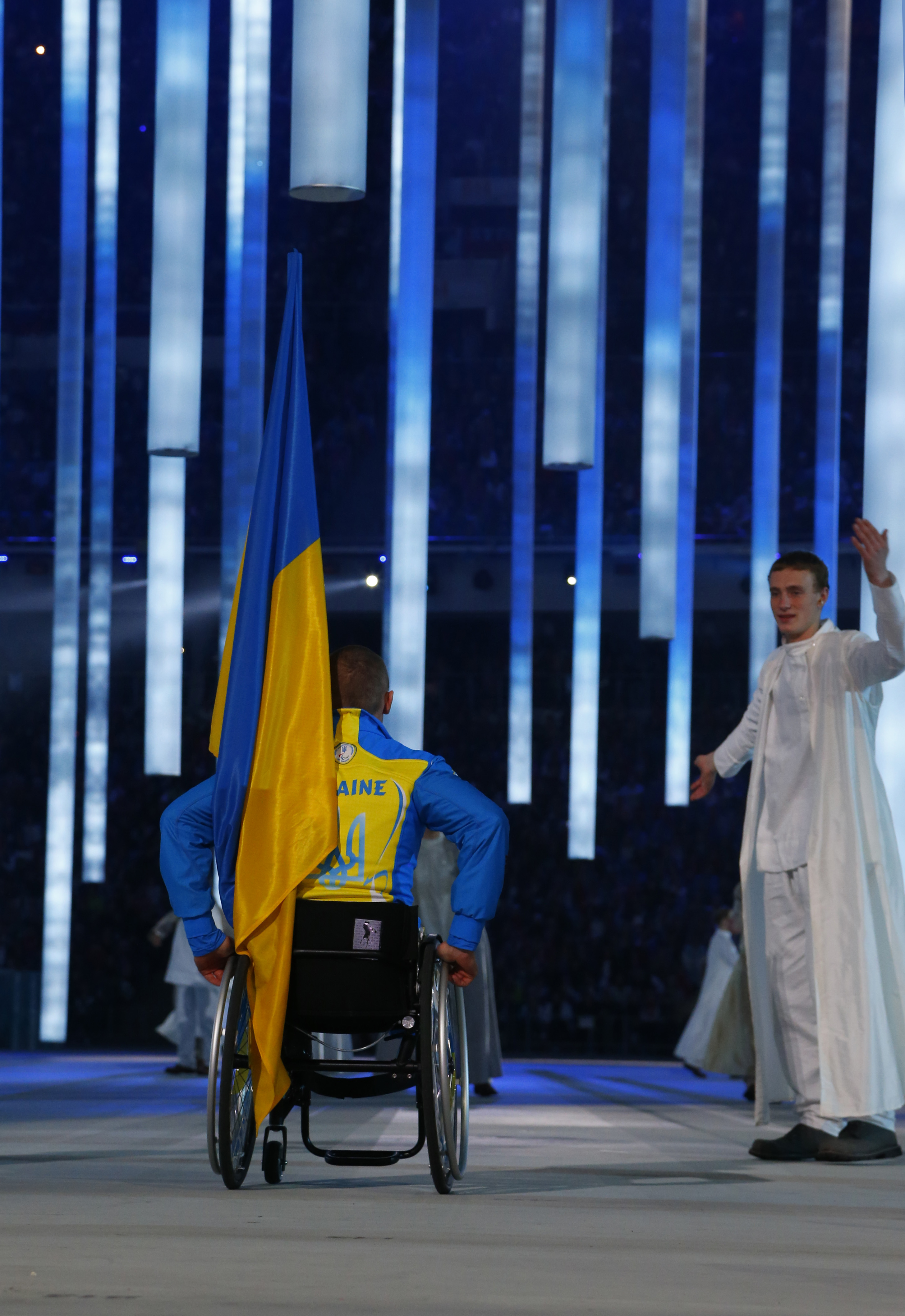 CAPTION ADDS NAME OF ATHLETE - Biathelete Mykhaylo Tkachenko, representing Ukraine, enters the arena during the opening ceremony of the 2014 Winter Paralympics at the Fisht Olympic stadium  in Sochi, Russia, Friday, March 7, 2014.  (AP Photo/Dmitry Lovetsky)