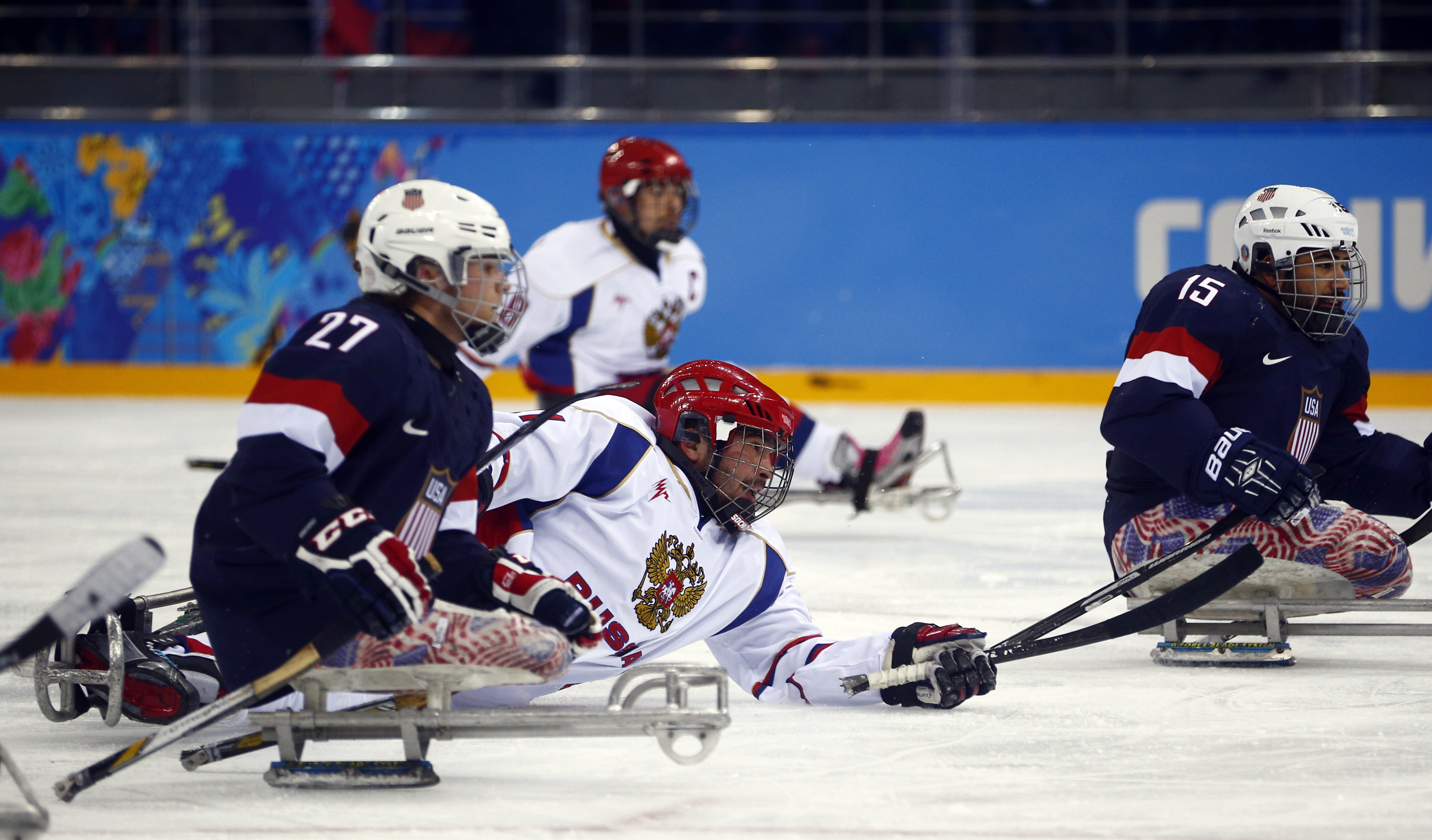Russia's Evgeny Petrov, center, shoots on goal as United States' Joshua Pauls, left, makes a challenge during an ice sledge hockey match between United States and Russia at the 2014 Winter Paralympics in Sochi, Russia, Tuesday March 11, 2014. (AP Photo/Pavel Golovkin)