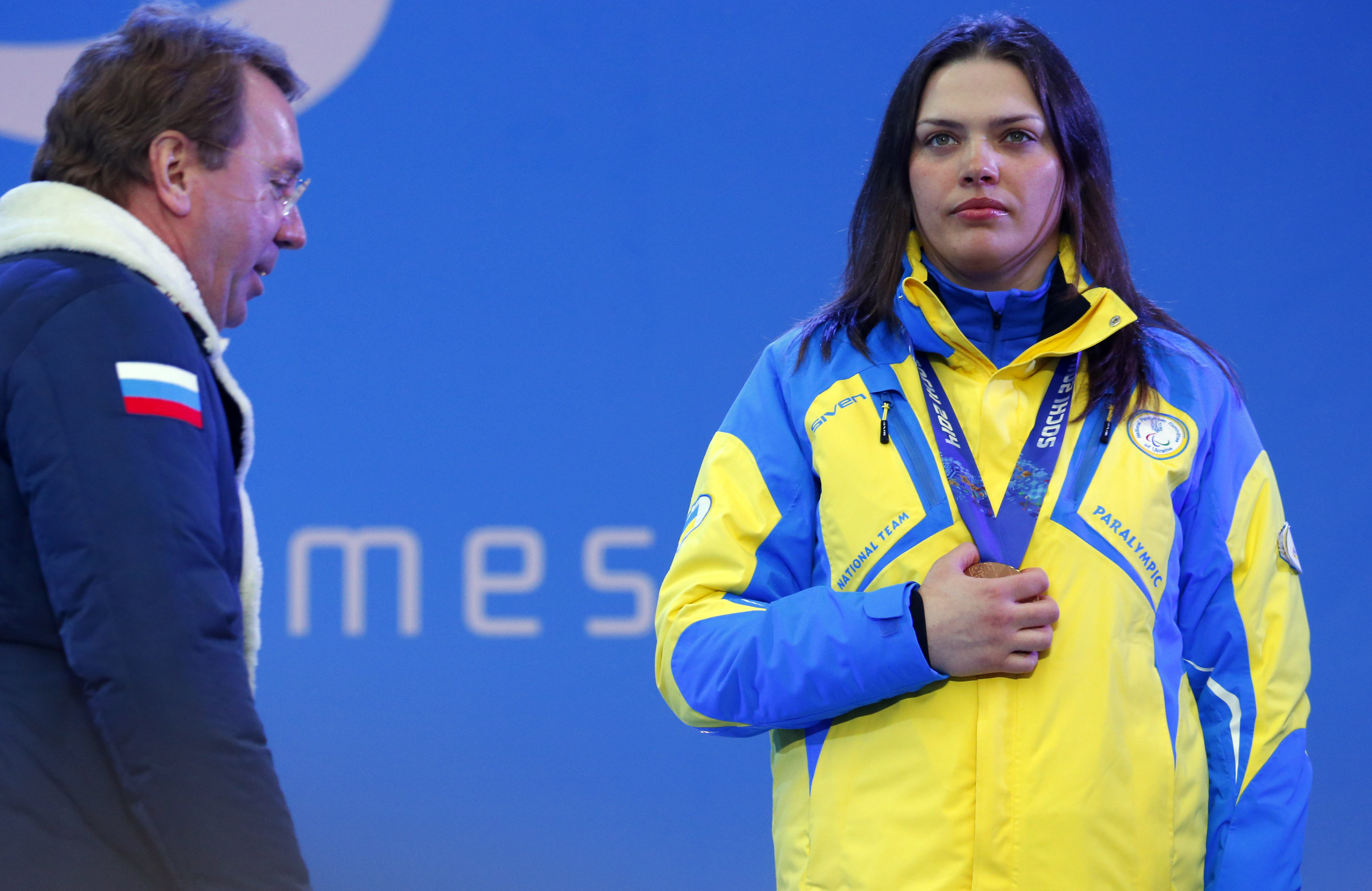 Ukraine's Olena Iurkovska covers her bronze medal with her hand after finishing third in the women's biathlon 12,5 km sitting as Kremlin Chief Property Manager Vladimir Kozhin passes by during a medal ceremony at the 2014 Winter Paralympics, Friday, March 14, 2014, in Krasnaya Polyana, Russia. The majority of Ukraine's Paralympic medalists covered their medals during medal ceremonies. (AP Photo/Dmitry Lovetsky)