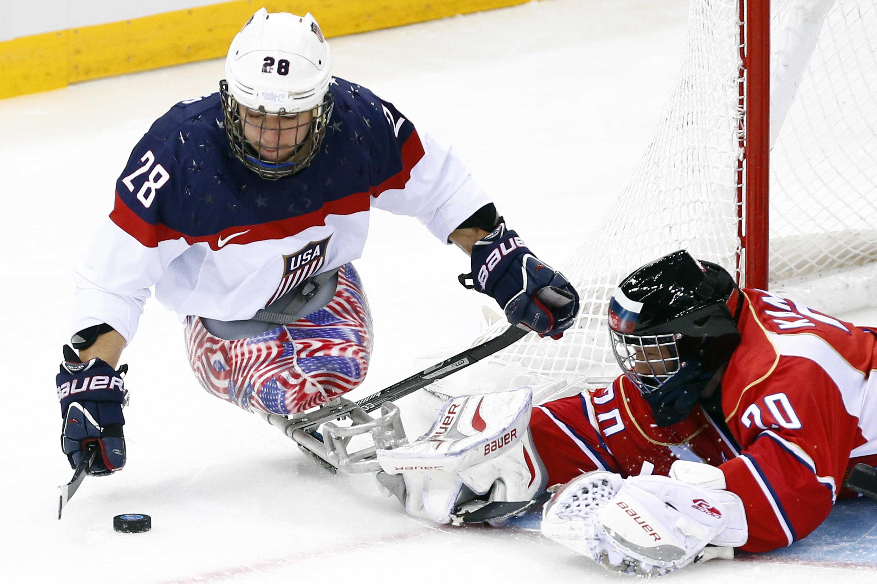 United States's Paul Schaus, left in action with Russia's Vladimir Kamantcev, right during the gold medal ice sledge hockey match between United States and Russia at the 2014 Winter Paralympics in Sochi, Russia, Saturday, March 15, 2014. (AP Photo/Pavel Golovkin)