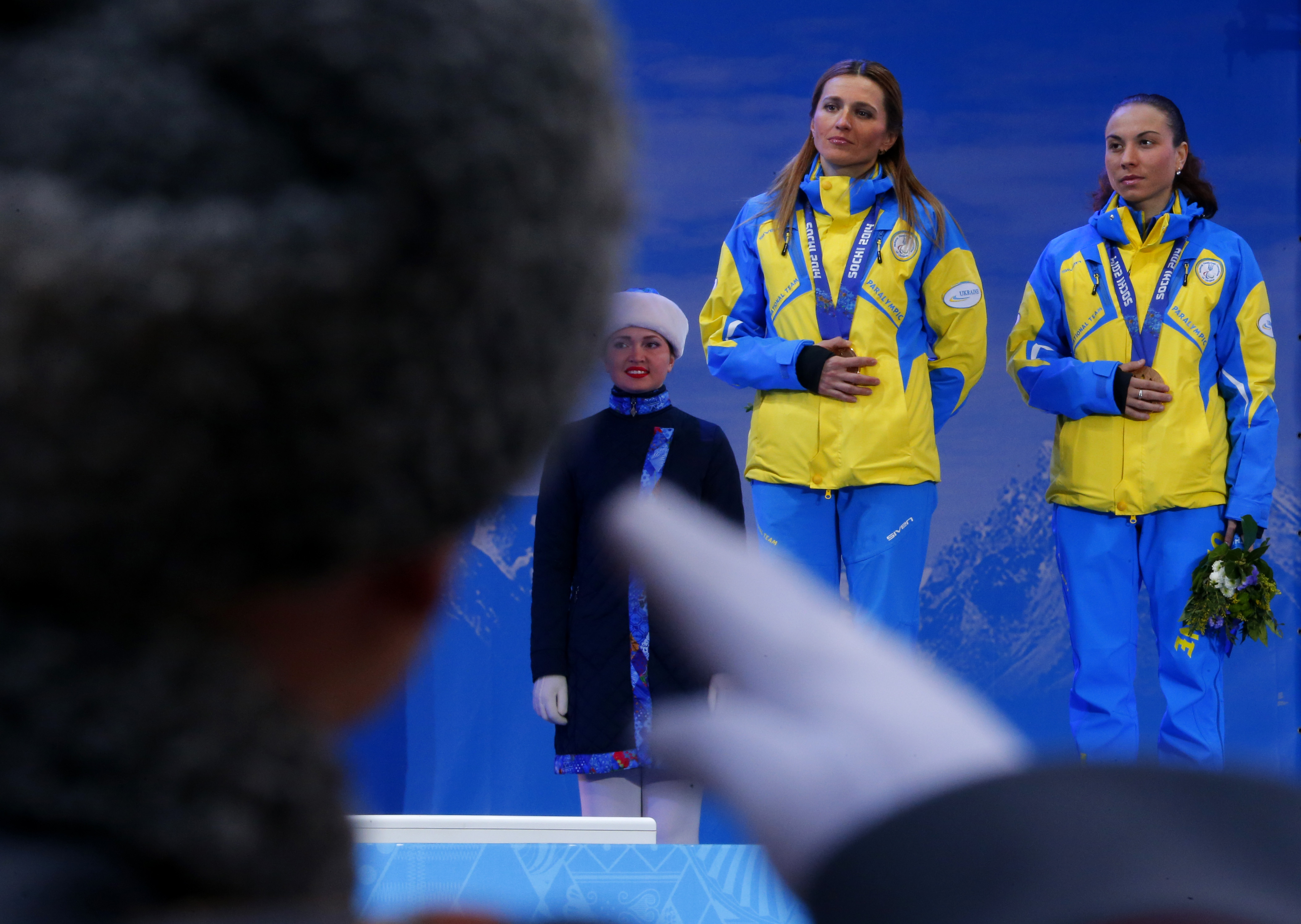 A Russian honor guard soldier salutes as Ukraine's  Oksana Shyshkova , right, and her guide Lada Nesterenko cover their bronze medals with their hands after winning 3 place in the women's biathlon 12,5 km visually impaired event during a medal ceremony at the 2014 Winter Paralympic, Saturday, March 15, 2014, in Krasnaya Polyana, Russia. The majority of Ukraine's Paralympic medalists covered their medals during medal ceremonies. (AP Photo/Dmitry Lovetsky)