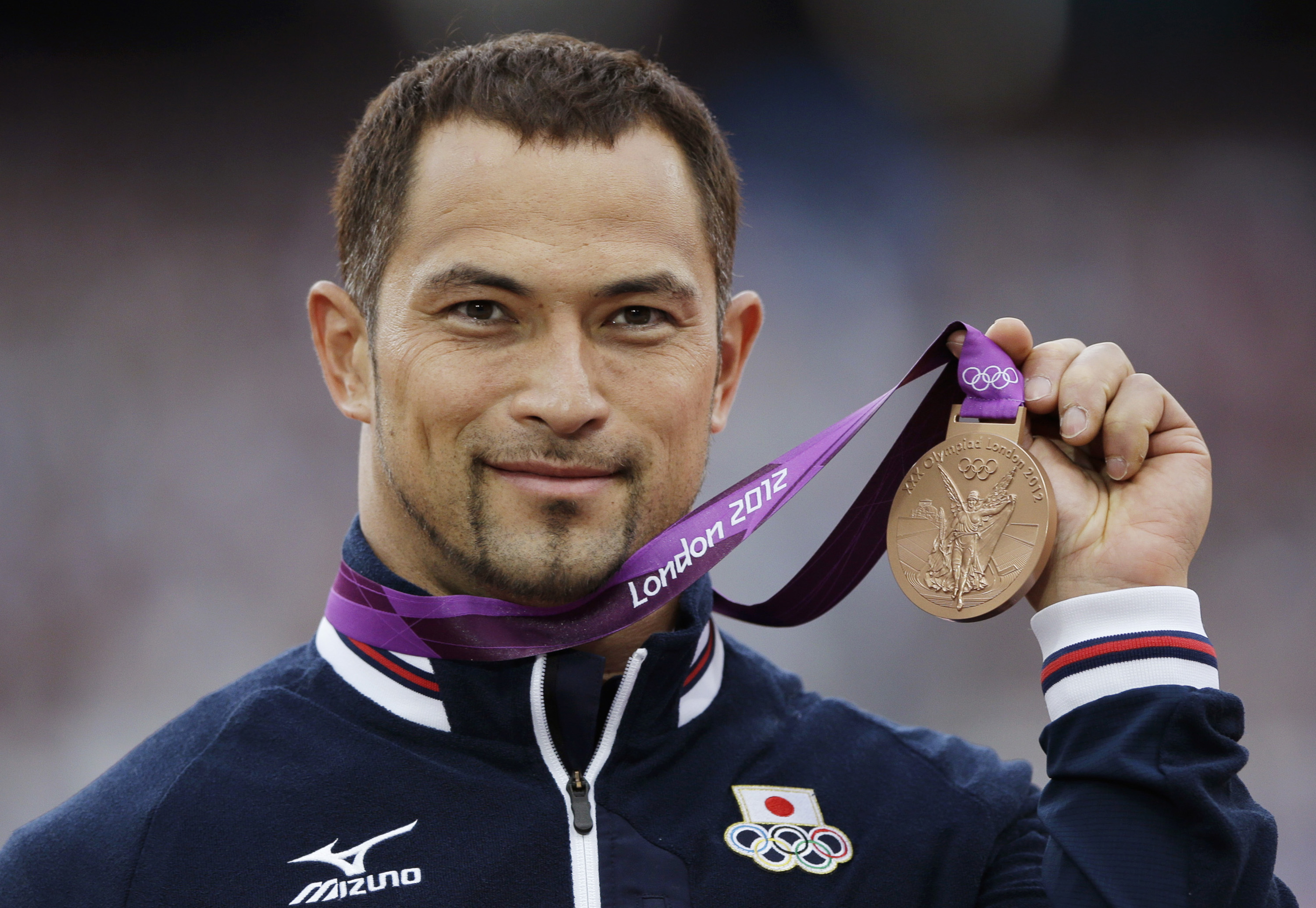 FILE - In this Monday, Aug. 6, 2012 file photo Japan's Koji Murofushi poses with his bronze medal for the men's hammer throw in the Olympic Stadium at the 2012 Summer Olympics in London. Olympic hammer-throw gold medalist Murofushi is among the Tokyo 2020 Olympics board members. (AP Photo/Matt Slocum, File)