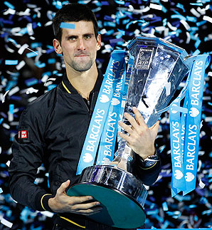 Novak Djokovic holds the ATP World Tennis trophy after defeating Roger Federer for the title.