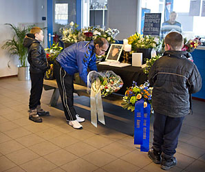A man puts down flowers at the condolence book for the linesman Richard Nieuwenhuizen on Saturday.