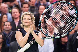 Kim Clijsters holds a giant racket as she greets her fans after winning her exhibition finale.