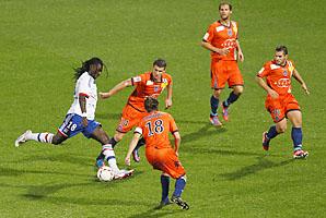 Bastia players surround Lyon's Bafe Gomis in a Ligue 1 match earlier this season.