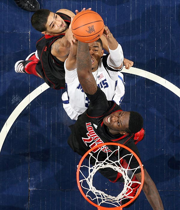 Memphis' D.J. Stephens jumps for a rebound against Louisville's Peyton Siva (3) and Montrezl Harrell. The Tigers let their lead slip away in the second half, falling to the Cardinals 87-78.