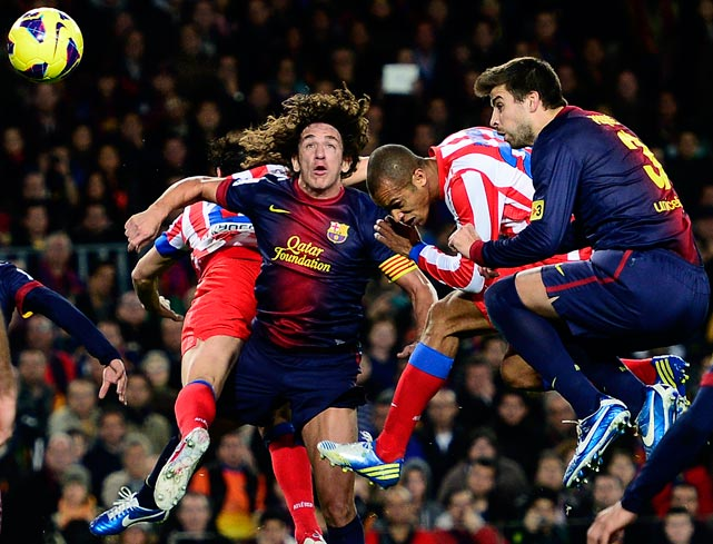 Madrid's Joao Mirando fights for the ball against Barcelona's Carles Puyol (left) and Gerard Pique.