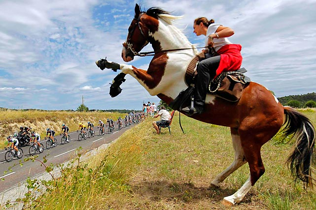 Tour de France cyclists ride past a woman on a horse.