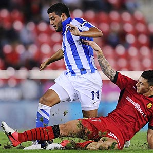 Real Sociedad's Carlos Vela duels with Joaquin Navarro of Mallorca in a La Liga match.