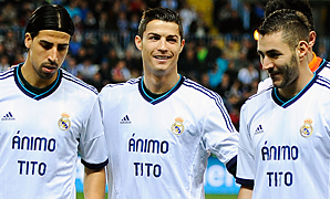 Real Madrid players, including Cristiano Ronaldo (center) support Barcelona coach Tito Vilanova before Saturday's match.