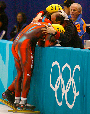 Guy Thibault (in black) celebrates with two Canadian speedskaters at the 2002 Olympics.