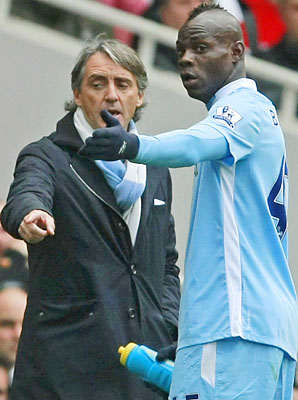 Roberto Mancini and Mario Balotelli chat during a Premier League match in 2012.