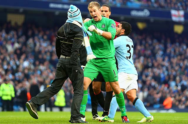 Joe Hart confronts a pitch invader during the Manchester derby on Dec. 9.