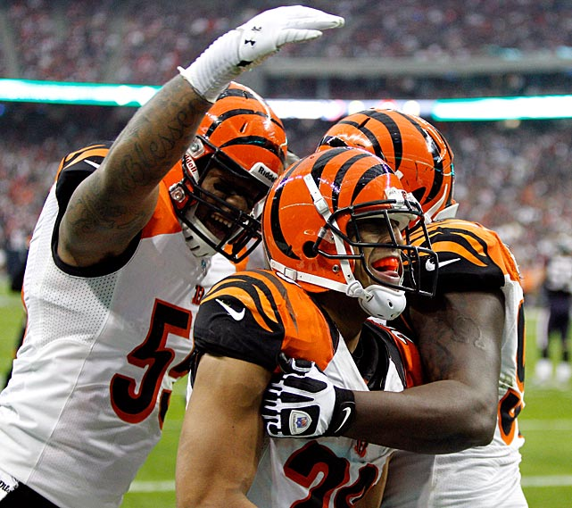 Leon Hall is congratulated by his teammates after scoring on a pick-6 to give Cincinnati a 7-6 lead in the second quarter.