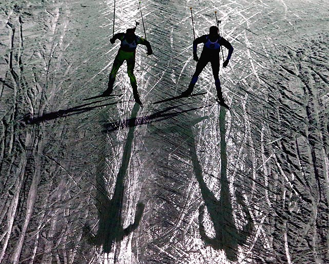 Two athletes compete in the dark in the men's 10km sprint event of the IBU Biathlon World Cup in Ruhpolding, Germany, on Jan. 12.