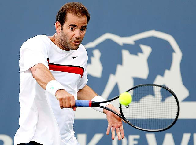 Pete Sampras returns a shot to Michael Chang while playing an exhibition match in 2012.