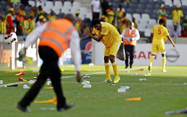 Ethiopia's Asrat Megersa (center) helps officials clear the pitch of vuvuzelas and plastic bottles.