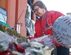 "A fan pays tribute to Stan ""The Man"" Musial, who passed away on Saturday. Cardinals' fans have flocked to Musial's statue to lay flowers and memorabilia."
