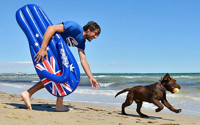 Jeremy Chardy plays with a dog on Port Melbourne Beach a day before his quarterfinal with Andy Murray.