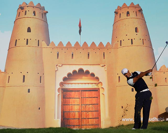 Standing in front of a picture poster, Tiger Woods tees off on the 15th hole during the first round of the Abu Dhabi Golf Championship. Woods missed the cut at the tournament after incurring a two-stroke penalty for taking an incorrect drop in his second round, pushing his score one above the cut line.