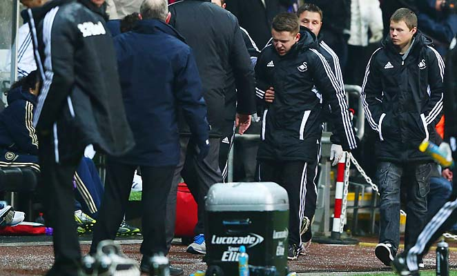 The ball boy kicked by Eden Hazard walks off the pitch.
