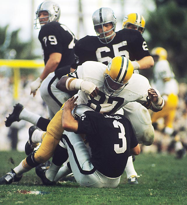 Green Bay Packers defensive end Willie Davis takes down Oakland Raiders quarterback Daryle Lamonica for a sack. The Packers' staunch defense limited the Raiders to 293 yards of offense in Green Bay's 33-14 win.