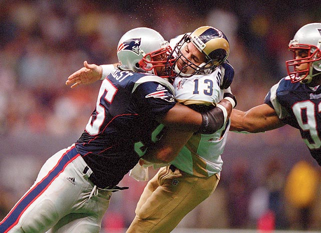 New England Patriots linebacker Willie McGinest crashes into Kurt Warner as defensive tackle Richard Seymour closes in from behind. Warner, leading the Greatest Show on Turf offense, threw for 365 yards with two total touchdowns but also tossed two interceptions in the Rams' 20-17 loss.