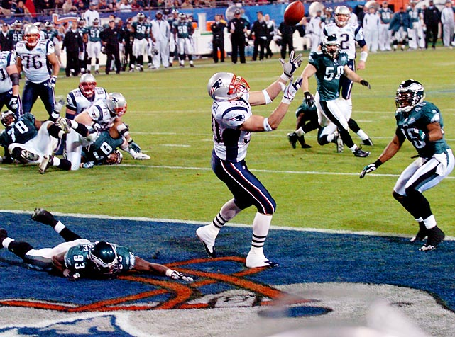 New England Patriots linebacker and tight end Mike Vrabel reaches for a floating pass from Tom Brady in the end zone. Vrabel's touchdown grab put the Patriots up 14-7 in the third quarter. On defense, Vrabel's primary duties, he sacked Philadelphia Eagles quarterback Donovan McNabb for a 16-yard loss. The Patriots won 24-21.